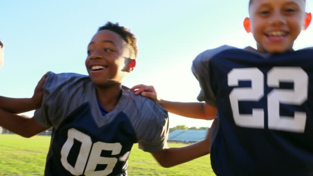 ZO MS Laughing young football players standing with teammates on field before game