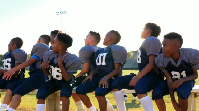 ms laughing young football teammates sitting on bench together - bench stock videos & royalty-free footage