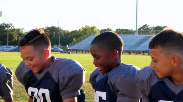 MS Laughing young football teammates sitting together on bench while passing football before practice