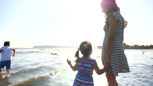 vídeos y material grabado en eventos de stock de ms laughing young girl playing in surf with mother and brother - familia con dos hijos
