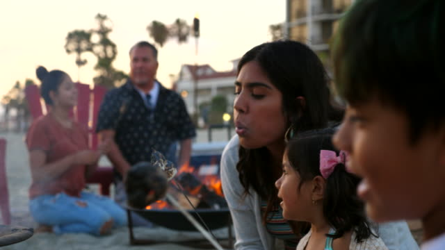 cu laughing young girl roasting marshmallow with mother during beach party - latin american and hispanic ethnicity stock videos & royalty-free footage