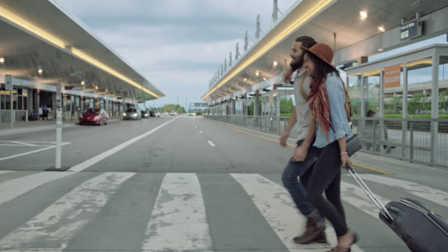 Laughing young hip couple walks through crosswalk to airport terminal rolling suitcase.