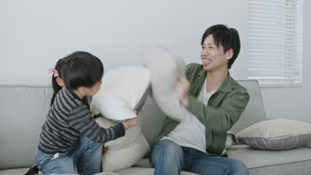 laughing young japanese family having pillow fight on sofa - randoseru stock videos & royalty-free footage