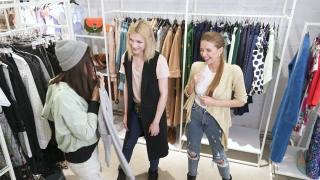 laughing young women and their transgender friend shopping in boutique - shirt stock videos and b-roll footage