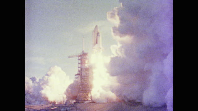 vídeos de stock e filmes b-roll de launch clouds fill the sky as the shuttle soars into outer space eventually breaking away from the rocket. space dirt and rocks float above as the... - 1981