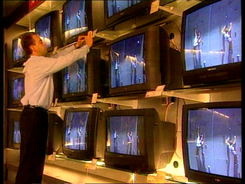 launch of the single european currency - the euro; belgium: gv display of wall of televisions in shop as man affixes a price card to one of them... - bericht film und fernsehen stock-videos und b-roll-filmmaterial