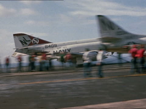 F4B launching with afterburners off USS Constellation / pan back to A4E waiting to launch