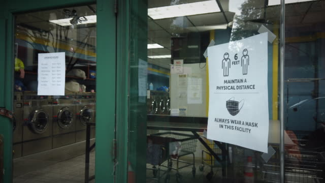"""laundromat business entrance door during coronavirus pandemic with a sign that reads: """"maintain a physical distance. always wear a mask in this... - entrance sign stock videos & royalty-free footage"""