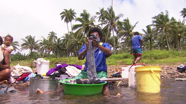 vídeos de stock, filmes e b-roll de laundry being scrubbed in river at village of naviavia fiji - contéiner de plástico