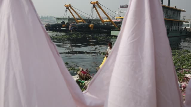 laundry clothes are washed in the polluted water of buriganga river in dhaka bangladesh on march 19 2018 the chemical waste of mills and factories... - bangladesch stock-videos und b-roll-filmmaterial