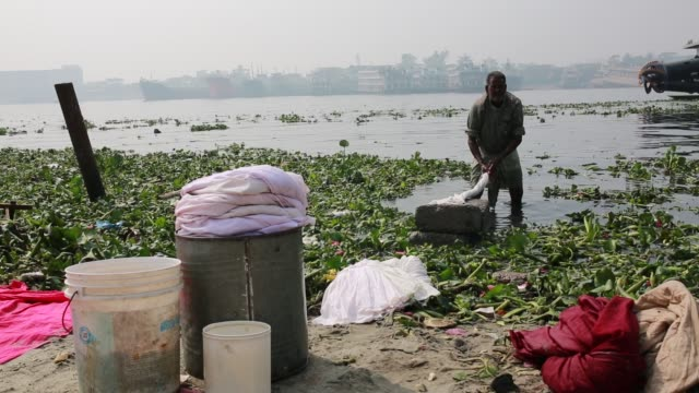 laundry clothes are washed in the polluted water of buriganga river in dhaka bangladesh on march 19 2018 the chemical waste of mills and factories... - demobilisation stock videos & royalty-free footage