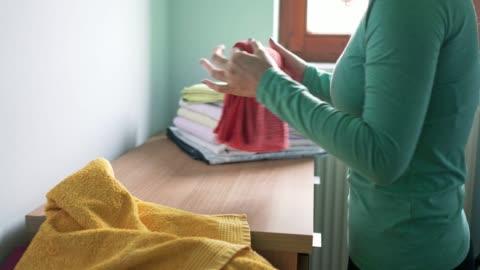 vidéos et rushes de jour de lessive - femme pliant lavé serviettes - laver