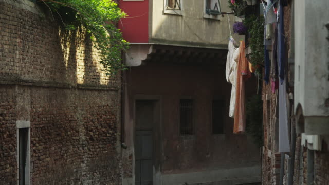 vidéos et rushes de ms tu laundry drying on washing line above street / venice,veneto - mur brique