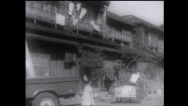 laundry hangs from a row of houses near tsukudajima, japan. - 1950 1959 stock-videos und b-roll-filmmaterial