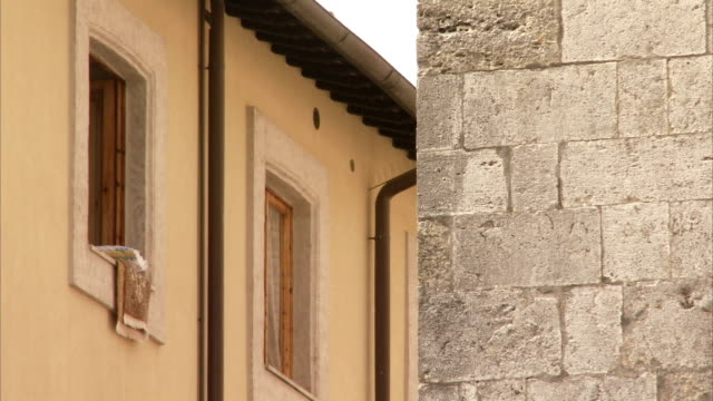 laundry hangs from a window across from a stone building in montepulciano, italy. available in hd. - montepulciano stock videos & royalty-free footage