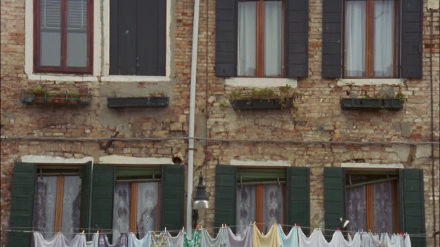 Laundry hangs from clotheslines stretched from window to window in Venice, Italy.