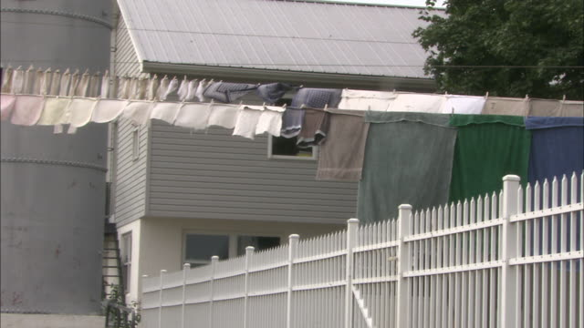 Laundry on a clothesline waves in the breeze above a white picket fence on an Amish farm.