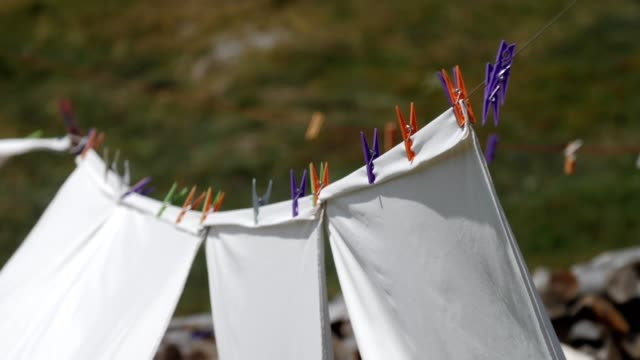 laundry on clothesline in the nature, clothing drying outside in the wind, white sheets hanging on clothesline, - washing line stock videos and b-roll footage