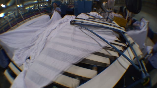 laundry workers sort laundry and place it onto conveyor belts. - lavanderia pubblica video stock e b–roll