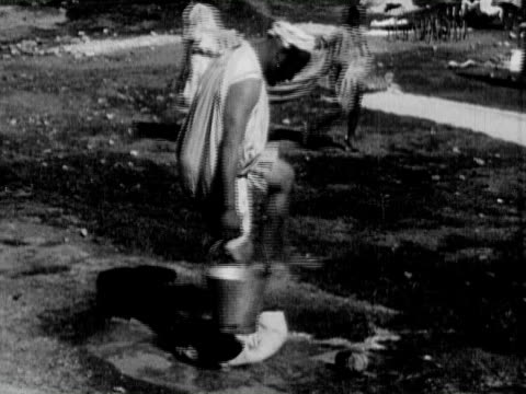 1934 b/w montage ms laundrymen stomping on laundry with feet, beating piles of clothes with clubs / india - kufi stock videos & royalty-free footage