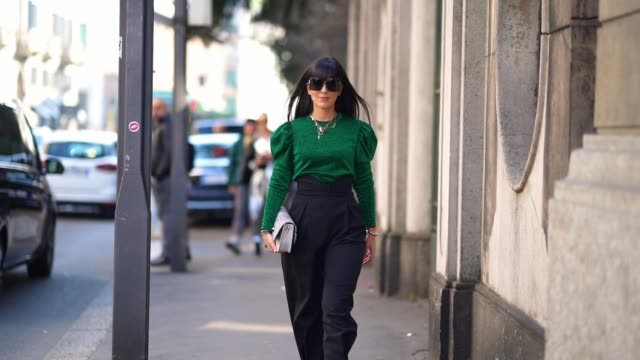 stockvideo's en b-roll-footage met laura comolli wears sunglasses, necklaces, bracelets, a heather forest-green top with puff sleeves, high-rise black pleated pants, black pointy... - mouw