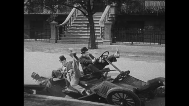 1931 laurel & hardy pull up in front of house just as car falls apart - fernsehserie stock-videos und b-roll-filmmaterial