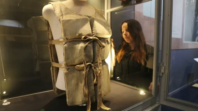 lauren hogan looks at lifebelt from the titanic, one of only a couple that remain in existence, that was given by a survivor to a waiter working on... - タイタニック号点の映像素材/bロール