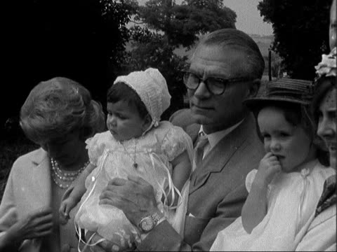laurence olivier and joan plowright attend daughter's christening; england: west sussex: lavant: ext laurence olivier carries baby towards - followed... - ローレンス オリビエ点の映像素材/bロール