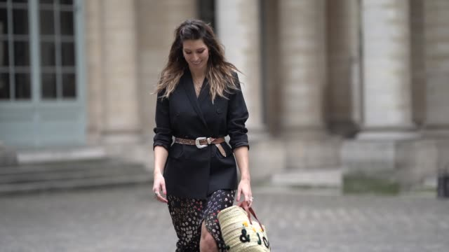 Laury Thilleman wears a black blazer jacket a brown belt a straw bag a floral print skirt black leather boots outside Paul Joe during Paris Fashion...