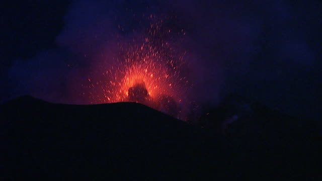 Lava and ash erupt from volcano at night, New Britain, PNG