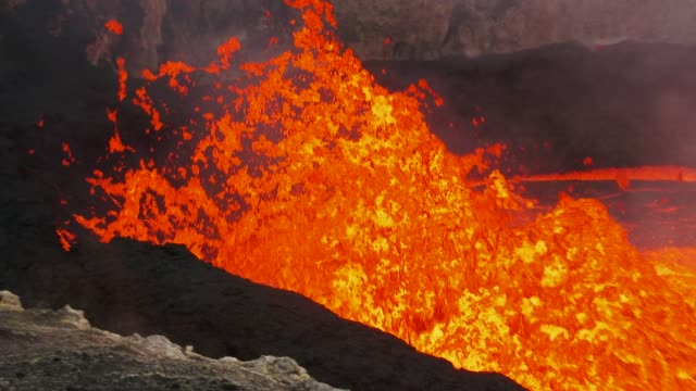 lava bursts towards the ashy edge of lava lake - vulkanausbruch stock-videos und b-roll-filmmaterial