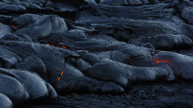 lava cools as darkness falls. available in hd. - lava stock-videos und b-roll-filmmaterial