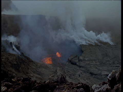 lava erupting from earth in smoking lava field, hawaii - vulkanausbruch stock-videos und b-roll-filmmaterial