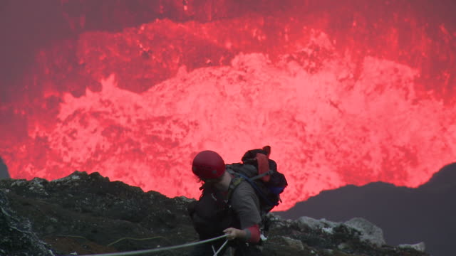 lava erupts from volcano behind climber, marum volcano, ambrym island, vanuatu - approaching stock videos & royalty-free footage