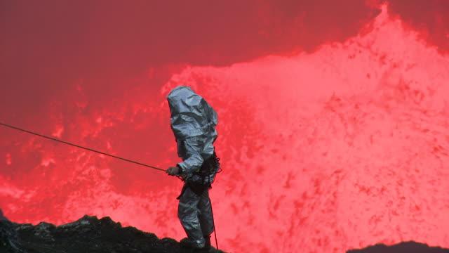 Lava erupts vigorously behind volcanologist , Marum Volcano, Ambrym Island, Vanuatu