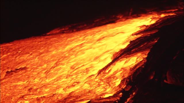 a lava flow pours through rocks. - lava stock videos & royalty-free footage