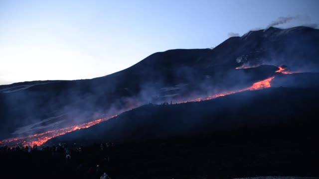 lava flows from a fracture at the base of southeast crater of volcano etna as its eruption activity continues on april 2 2017 in catania italy until... - vulkanausbruch stock-videos und b-roll-filmmaterial