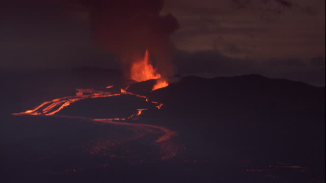 lava flows from a volcano erupting in the distance. available in hd. - volcano stock videos & royalty-free footage