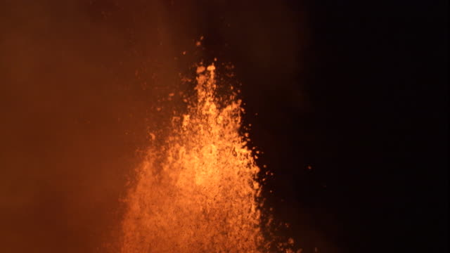 Lava from a volcanic eruption spews into the night sky. Available in HD.