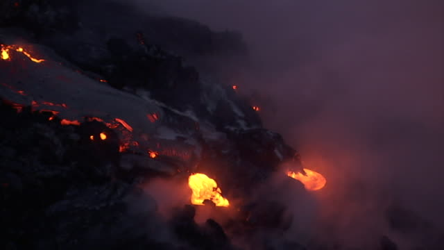 lava from a volcano glows orange below racing smoke on hawaii's big island. - lava stock videos & royalty-free footage