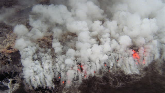 lava from a volcano spills into an ocean from river banks. - red tape stock videos & royalty-free footage
