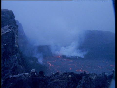 vídeos de stock, filmes e b-roll de lava spews from volcanic fissure as night falls, hawaii - forma da água