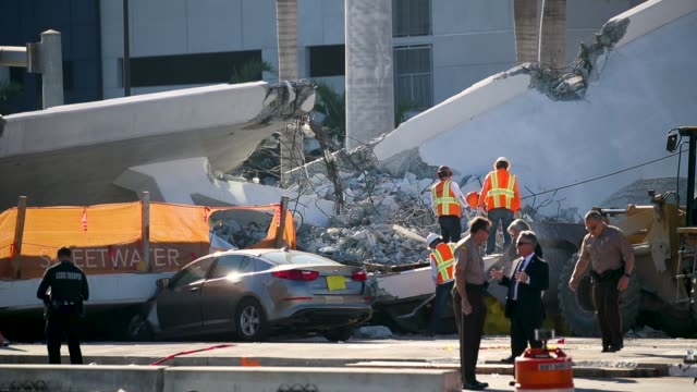 law enforcement and members of the national transportation safety board continue their investigation into a pedestrian bridge that collapsed... - bridge built structure stock videos & royalty-free footage