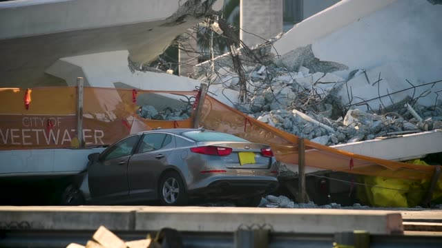 law enforcement and members of the national transportation safety board continue their investigation into a pedestrian bridge that collapsed... - bridge built structure stock videos and b-roll footage