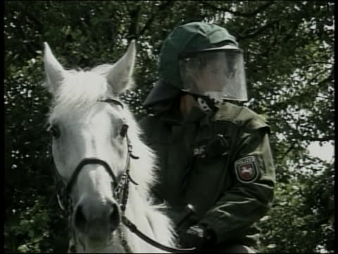 a law enforcement officer in riot gear patrols on horseback during protests at the 2007 g8 summit in rostock laage germany - (war or terrorism or election or government or illness or news event or speech or politics or politician or conflict or military or extreme weather or business or economy) and not usa stock-videos und b-roll-filmmaterial