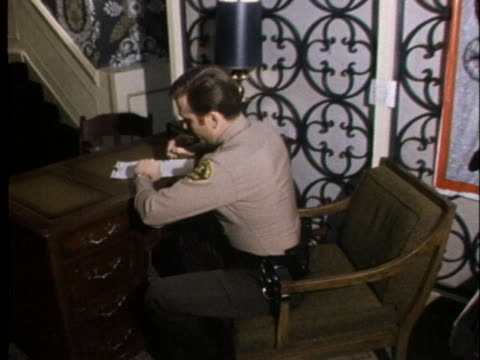 a law enforcement officer sits at a small desk in front of a christmas poster at the hotel in which charles manson's jury is staying - christmas poster stock videos & royalty-free footage