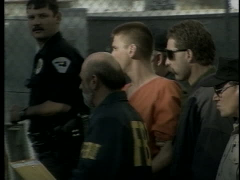law enforcement officers lead the handcuffed terrorist suspect timothy mcveigh to a waiting van. - oklahoma city bombing stock videos & royalty-free footage