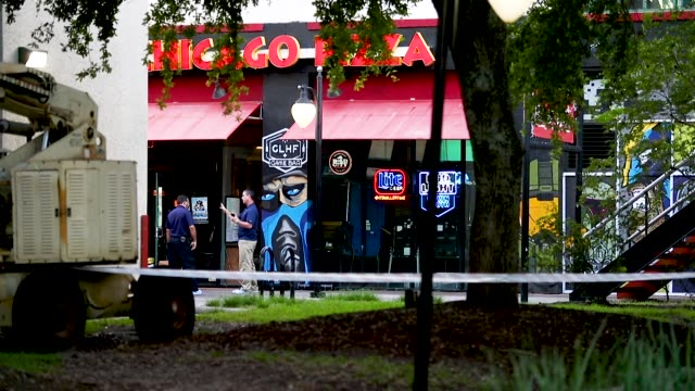 law enforcement officials investigate a shooting in the glhf game bar where 3 people including the gunman were killed at the jacksonville landing on... - jacksonville florida video stock e b–roll