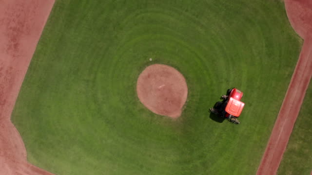 lawn mower is working on baseball green field. camera is rotating around. - tagliaerba video stock e b–roll