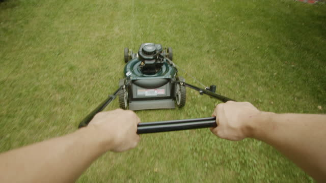 lawn mower point of view human hands sunset summer grass garden - lawn mower stock videos and b-roll footage